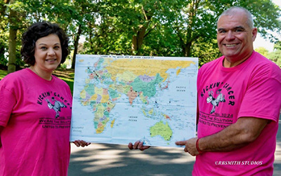 Rebecca and Baron holding up a map of the world