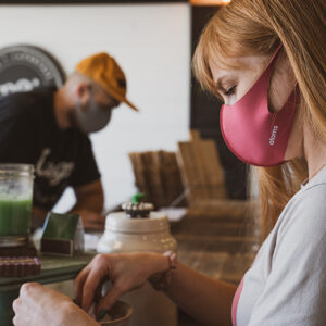Woman sitting at coffee bar with a pink face mask