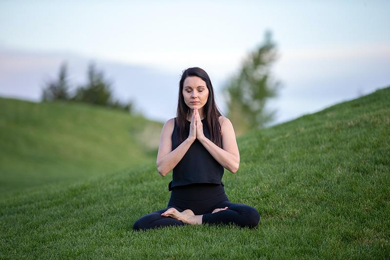 Woman doing yoga in green grass