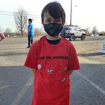 Young boy with a face mask and red kicking cancer shirt